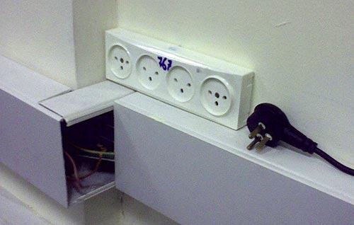Mains socket strip mounted above a conduit
